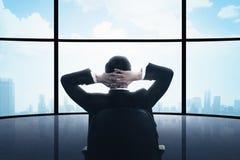 Uomo di affari che si siede sulla sedia che guarda la finestra Fotografie Stock