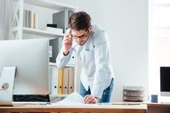 Uomo di affari che sta allo scrittorio che lavora ai documenti con il cellulare Fotografie Stock