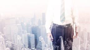 Uomo di affari che sta sul tetto con la città nei precedenti Fotografia Stock