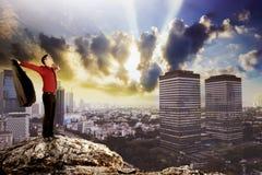 Uomo di affari che sta sulla cima della roccia Fotografia Stock Libera da Diritti