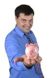 Uomo di affari che tiene banca piggy Fotografia Stock