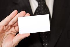 Uomo di affari che tiene businesscard in bianco Immagini Stock