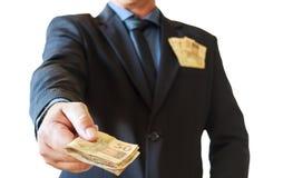 Uomo di affari che tiene il brasiliano dei soldi in sue mani ed in tasca del vestito Priorità bassa bianca immagine stock