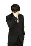Uomo di affari che tiene la sua testa nel dolore contro fotografia stock