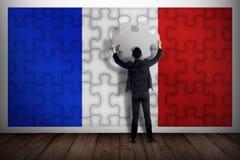 Uomo di affari che tiene pezzo di puzzle, facente la bandiera del francese Immagine Stock