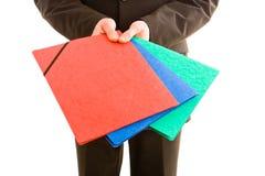 Uomo di affari che tiene tre dispositivi di piegatura colourful immagini stock