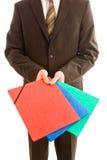 Uomo di affari che tiene tre dispositivi di piegatura colourful Fotografie Stock Libere da Diritti