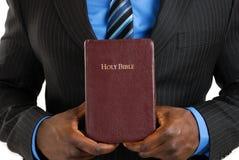 Uomo di affari che tiene una bibbia Immagini Stock