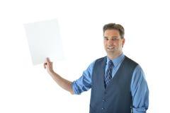 Uomo di affari che tiene una carta bianca in bianco Immagine Stock