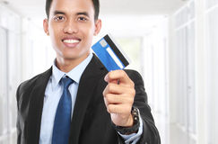 Uomo di affari che tiene una carta di credito e un sorriso fotografia stock