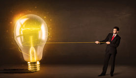 Uomo di affari che tira una grande lampadina d'ardore luminosa Fotografie Stock