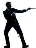 Uomo di affari che tira una siluetta della corda Fotografia Stock