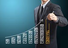 Uomo di affari che traccia un grafico crescente Immagini Stock