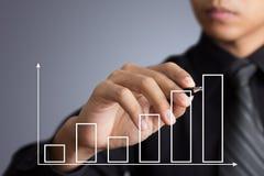 Uomo di affari che traccia un grafico di crescita Fotografia Stock Libera da Diritti