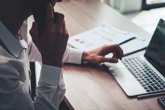 Uomo di affari che usando computer e cellulare sulla tavola con l'affare Immagine Stock
