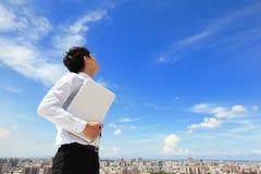 Uomo di affari che usando computer portatile e sguardo al cielo blu Immagine Stock Libera da Diritti