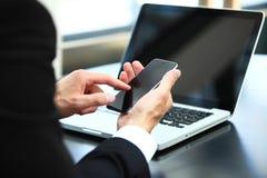 Uomo di affari che usando Internet sullo Smart Phone e sul computer portatile fotografie stock
