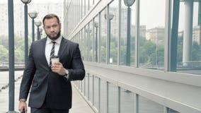 Uomo di affari con caffè che cammina vicino all'edificio per uffici video d archivio