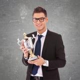 Uomo di affari con i vetri che tengono un grande trofeo Immagine Stock