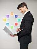 Uomo di affari con il computer portatile a disposizione e l'icona di media Fotografia Stock Libera da Diritti