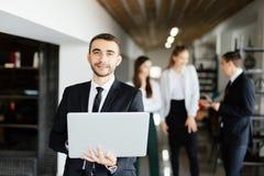 Uomo di affari con il computer portatile in mani davanti a discutere i colleghi Fotografia Stock