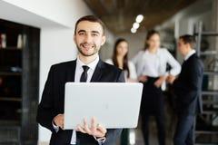 Uomo di affari con il computer portatile in mani davanti a discutere i colleghi Fotografia Stock Libera da Diritti