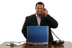 Uomo di affari con il computer portatile sul telefono Immagine Stock