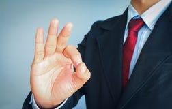 Uomo di affari con il legame rosso in vestito che mostra segno GIUSTO su fondo grigio, riuscito concetto Immagine Stock