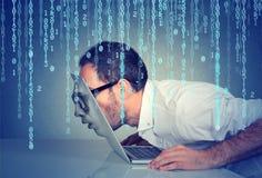 Uomo di affari con il suo fronte che passa tramite lo schermo di un computer portatile sul fondo di codice binario fotografia stock libera da diritti