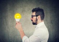 Uomo di affari con l'espressione premurosa che esamina la lampadina della luce intensa fotografie stock libere da diritti