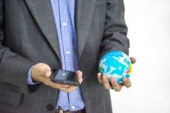 Uomo di affari con l'isolato del globo della terra e del telefono del moblie su bianco Fotografie Stock Libere da Diritti