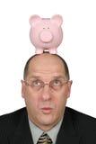 Uomo di affari con la Banca Piggy sulla testa Immagini Stock Libere da Diritti