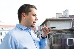 Uomo di affari con la camicia blu facendo uso di riconoscimento della voce in Smart Phone nel balcone fotografia stock libera da diritti