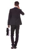 Uomo di affari con la cartella che comunica sullo smartphone Fotografie Stock Libere da Diritti