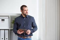 Uomo di affari con la compressa che guarda fuori la finestra Fotografia Stock