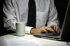 Uomo di affari con la tazza di caffè che lavora al computer portatile Immagine Stock