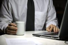Uomo di affari con la tazza di caffè che lavora al computer portatile Immagini Stock Libere da Diritti