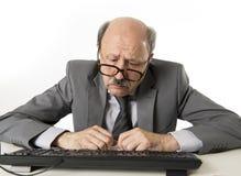 Uomo di affari con la testa calva sul suo funzionamento 60s sollecitato e frustrato allo scrittorio del computer portatile del co fotografia stock libera da diritti