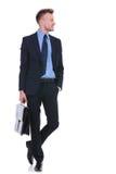Uomo di affari con la valigia e la mano in tasca Immagini Stock
