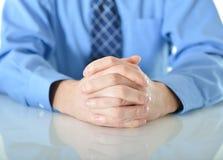 Uomo di affari con le mani attraversate che riposano sulla tavola Fotografia Stock Libera da Diritti
