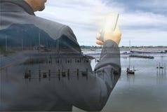 Uomo di affari con lo smartphone sul fondo dell'azienda agricola del gamberetto Fotografia Stock