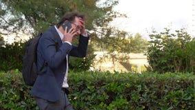 Uomo di affari con lo zaino che cammina nel parco in città che parla sul telefono felice stock footage