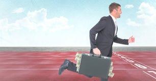 Uomo di affari con soldi che attaccano dalla cartella sulla pista contro il cielo Immagini Stock