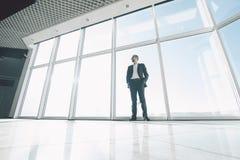 Uomo di affari contro le finestre panoramiche immagini stock