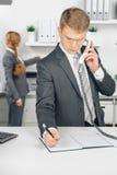 Uomo di affari di Attraktiv che parla al telefono in ufficio Immagine Stock Libera da Diritti