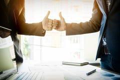 Uomo di affari di due giovani un pollice sul segno durante la discussione un meeti Immagine Stock
