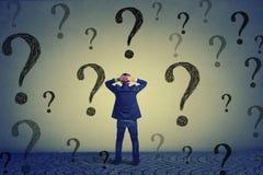Uomo di affari di retrovisione che sta davanti alla parete con molte domande Immagini Stock