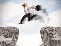 Uomo di affari divertenti che salta sopra le rocce con la lacuna Immagini Stock Libere da Diritti