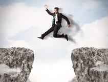 Uomo di affari divertenti che salta sopra le rocce con la lacuna Fotografie Stock
