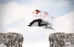 Uomo di affari divertenti che salta sopra le rocce con la lacuna Immagine Stock Libera da Diritti